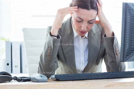 Upset business woman with head in hands in front of computer at officeの素材 [FYI00008277]