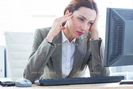 Upset business woman with head in hands in front of computer at officeの写真素材 [FYI00008278]