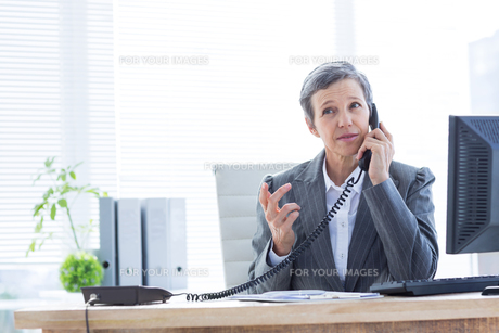 Serious businesswoman phoning and using computerの写真素材 [FYI00008282]