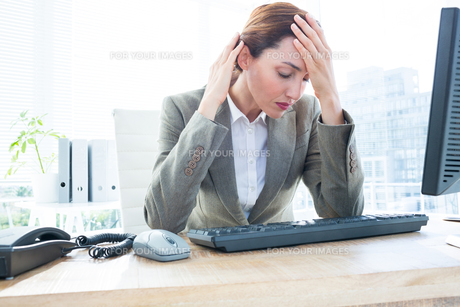 Upset business woman with head in hands in front of computer at officeの素材 [FYI00008283]