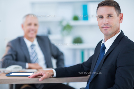 Confident businessman looking at camera with colleague behindの素材 [FYI00008306]