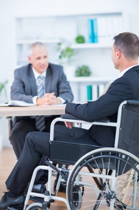 Businessman in wheelchair speaking with colleagueの素材 [FYI00008314]