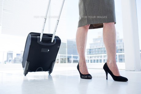 Businesswoman pulling her suitcase in the officeの写真素材 [FYI00008332]