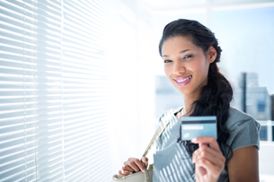 Smiling businesswoman looking at camera with credit cardの写真素材 [FYI00008333]
