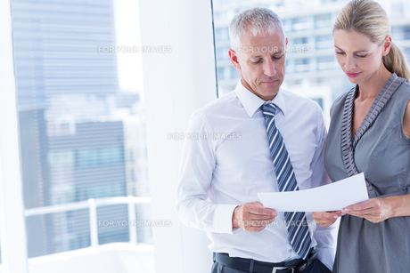 Business people talking over a paper sheetの写真素材 [FYI00008334]