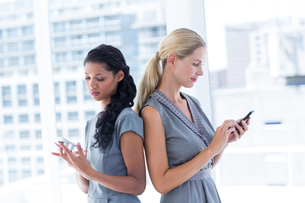 Back to back businesswomen texting messagesの写真素材 [FYI00008343]