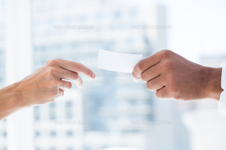 Hands giving small paper sheet to another oneの写真素材 [FYI00008346]