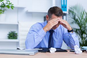 Businessman with severe headache sitting at office deskの写真素材 [FYI00008347]