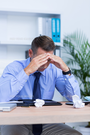 Businessman with severe headache sitting at office deskの写真素材 [FYI00008351]