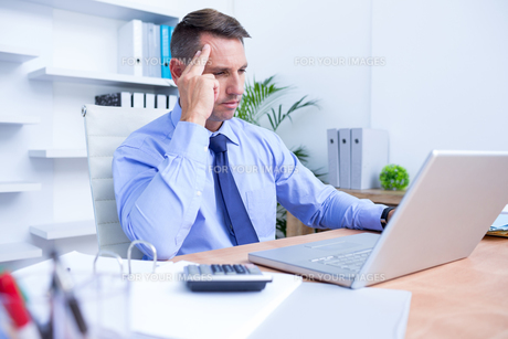 Businessman with severe headache sitting at office deskの写真素材 [FYI00008352]