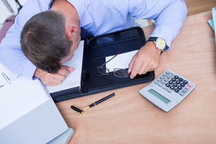 Exhausted businessman sleeping on the deskの写真素材 [FYI00008353]