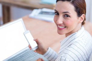 Brunette businesswoman smiling using laptop and her mobileの写真素材 [FYI00008380]