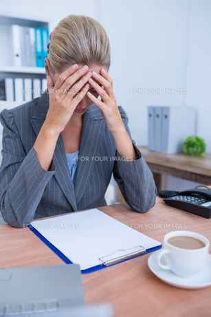 Pretty blonde businesswoman thinkingの写真素材 [FYI00008388]