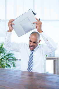 Irritated businessman about to break his laptopの写真素材 [FYI00008391]