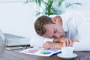 Exhausted businessman sleeping on the deskの写真素材 [FYI00008401]