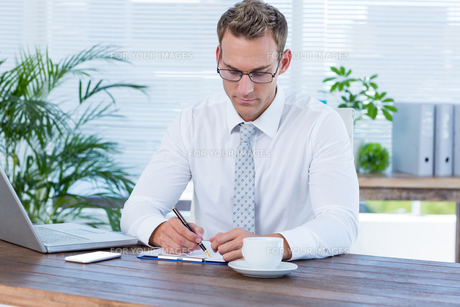 Concentrated businessman writing on a notebookの写真素材 [FYI00008403]