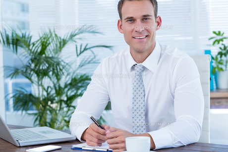 Smiling businessman writing on notebookの写真素材 [FYI00008405]