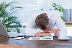 Exhausted businessman sleeping on the deskの写真素材 [FYI00008406]