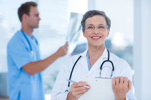 Smiling doctor holding a clipboardの写真素材 [FYI00008426]