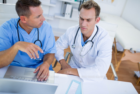 Concentrated medical colleagues discussing and working with laptopの写真素材 [FYI00008428]