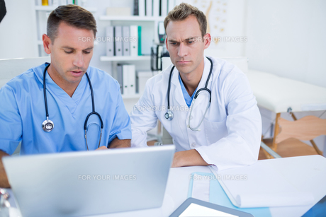 Concentrated medical colleagues working with laptopの写真素材 [FYI00008429]