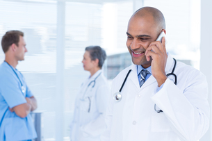 Smiling doctor talking on the phoneの写真素材 [FYI00008430]