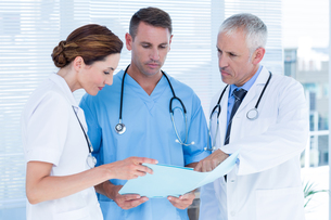 Concentrated medical colleagues analyzing file togetherの写真素材 [FYI00008431]