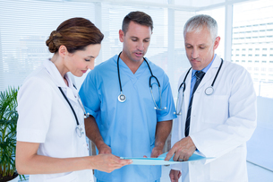 Concentrated medical colleagues analyzing file togetherの写真素材 [FYI00008432]