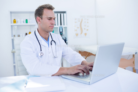 Focused doctor working with laptopの写真素材 [FYI00008433]