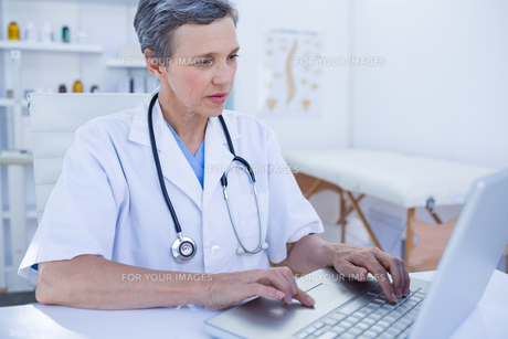 Serious female doctor using her laptop computerの写真素材 [FYI00008434]