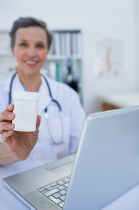 Female doctor holding a box of pillsの写真素材 [FYI00008435]