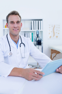 Happy doctor looking at camera and using tablet computerの写真素材 [FYI00008436]