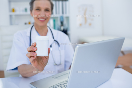 Female doctor holding a box of pillsの素材 [FYI00008440]