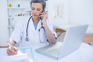 Female doctor having a phone callの写真素材 [FYI00008441]