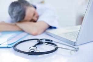 Female doctor sleeping on deskの写真素材 [FYI00008443]