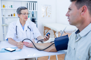 Doctor checking blood pressure of her patientの写真素材 [FYI00008452]