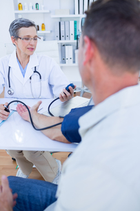 Doctor checking blood pressure of her patientの写真素材 [FYI00008453]
