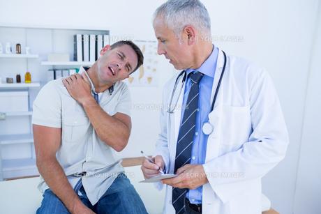 Doctor looking at patient shoulderの写真素材 [FYI00008457]