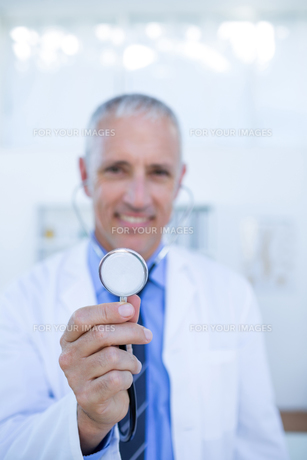 Happy doctor smiling at camera and showing his stethoscopeの写真素材 [FYI00008459]