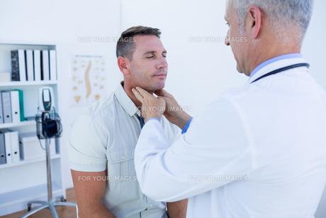 Doctor examining his patient neckの写真素材 [FYI00008460]
