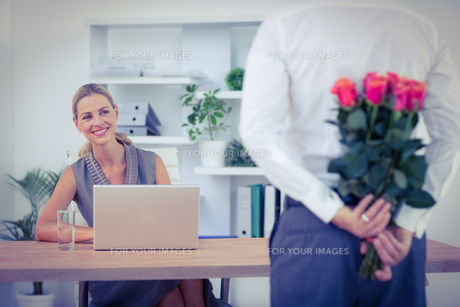Man hiding bouquet in front of businesswoman at deskの写真素材 [FYI00008464]