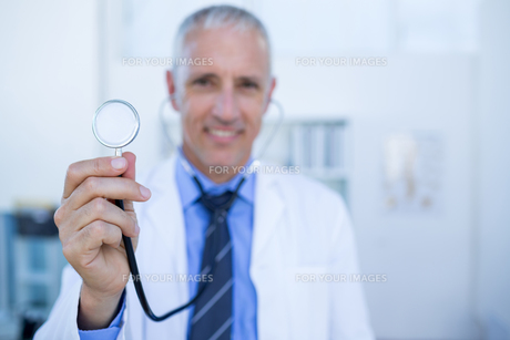 Happy doctor smiling at camera and showing his stethoscopeの写真素材 [FYI00008466]