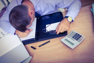 Exhausted businessman sleeping on the deskの写真素材 [FYI00008472]