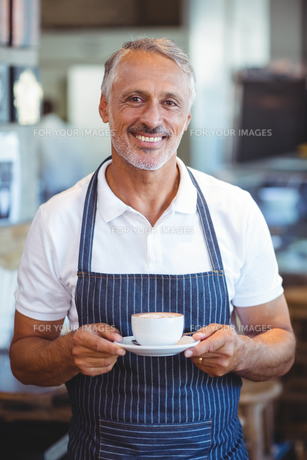 Waiter smiling and holding cup of coffeeの写真素材 [FYI00008694]