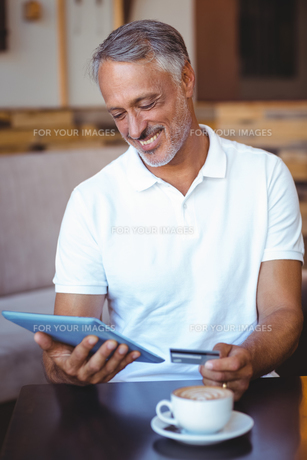 a customer holding tablet and credit cardの写真素材 [FYI00008701]