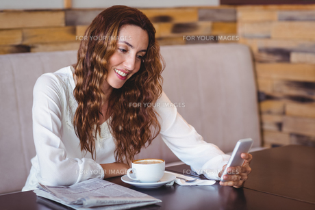 Woman using her mobile phone and holding cup of coffeeの写真素材 [FYI00008715]