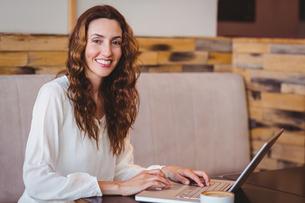 Pretty brunette having coffee using laptopの写真素材 [FYI00008718]
