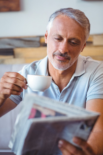 Smiling man having cup of coffee reading newspaperの素材 [FYI00008740]