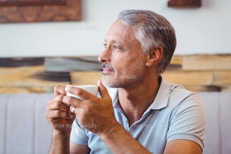 Man sitting in cafe having coffeeの写真素材 [FYI00008742]