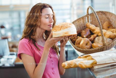 Pretty brunette smelling loaf of breadの写真素材 [FYI00008744]